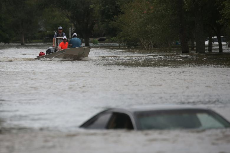 A rescue boat evacuates people from the rising waters of Buffalo Bayou following Hurricane Harvey in a neighborhood west of Houston